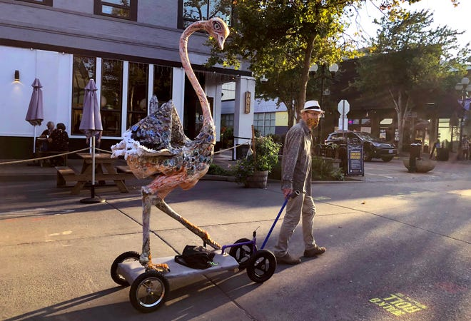 "Scott Parker takes ""Elvira"" the ostrich on his own personal ""walk your art"" tour down Broadway in downtown Eugene."