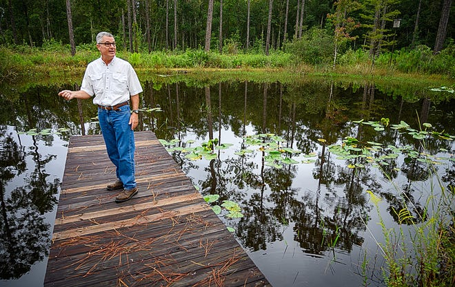 Mike Adams, an ecologist and former Land Acquisition and Management Program board member, stands on a dock of a pond on his 94-acre property off County Road 13 on Monday. [PETER WILLOTT/THE RECORD]
