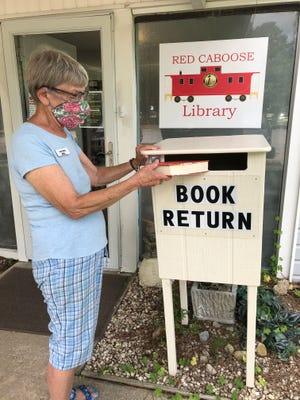 The Book Return at the entrance of the Library was made and donated by Christopher Organ.  Luci Avery is pictured returning a book. [CONTRIBUTED PHOTO]