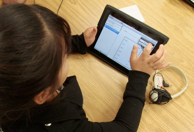 A young girl in a special education classroom reads a worksheet uploaded by her teacher to a tablet provided by the school district.