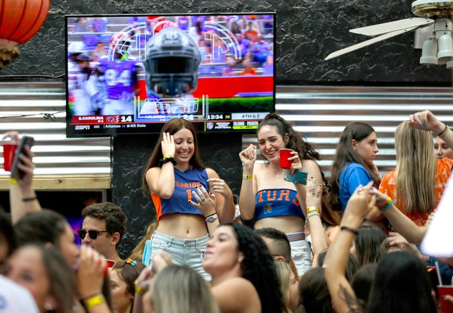 People dance and watch football inside of Lit at Midtown Restaurant and Patio Bar on Saturday in Gainesville. Lit was briefly closed down by the city of Gainesville over the weekend.