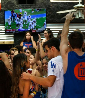 People dance and watch the football game inside of Lit at Midtown Restaurant and Patio Bar in Gainesville, Fla. on Oct. 3, 2020. Lit was closed down by City of Gainesville over the weekend.