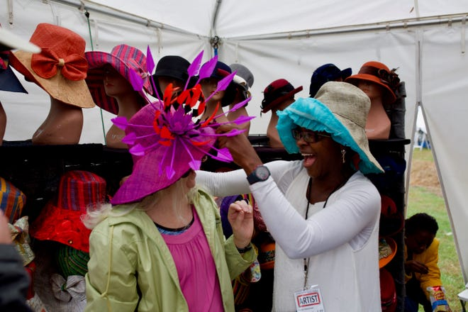 Cindy Kindley receives her recently purchased hat from Maryland based aritst Fatou Sall at the 47th annual Kentuck Arts Festival in 2018. This year's festival will be all virtual, beginning Saturday. [Photo/Joseph Field]