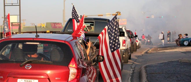 Vehicles carrying Trump and U.S. flags head east on North First Street into smoke created by burn-outs in front of them at the Willis Street intersection.  Oct 3 2020