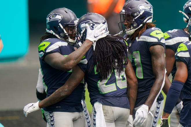 Seattle Seahawks cornerback Shaquill Griffin (26) is congratulated by his teammates after he intercepted a pass, during the second half of an NFL football game against the Miami Dolphins, Sunday, Oct. 4, 2020, in Miami Gardens, Fla. (AP Photo/Lynne Sladky)
