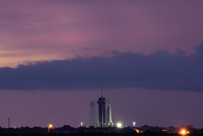 Purple skies are seen behind Kennedy Space Center's pad 39A early Monday, Oct. 5, 2020, but conditions quickly deteriorated enough to force SpaceX to scrub the launch of a Falcon 9 rocket with 60 Starlink satellites.