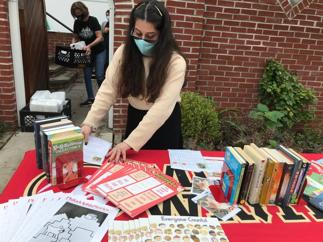 Volunteer Tiffany Veliz sets up a table with children's books and information about Mighty Writers in Camden.