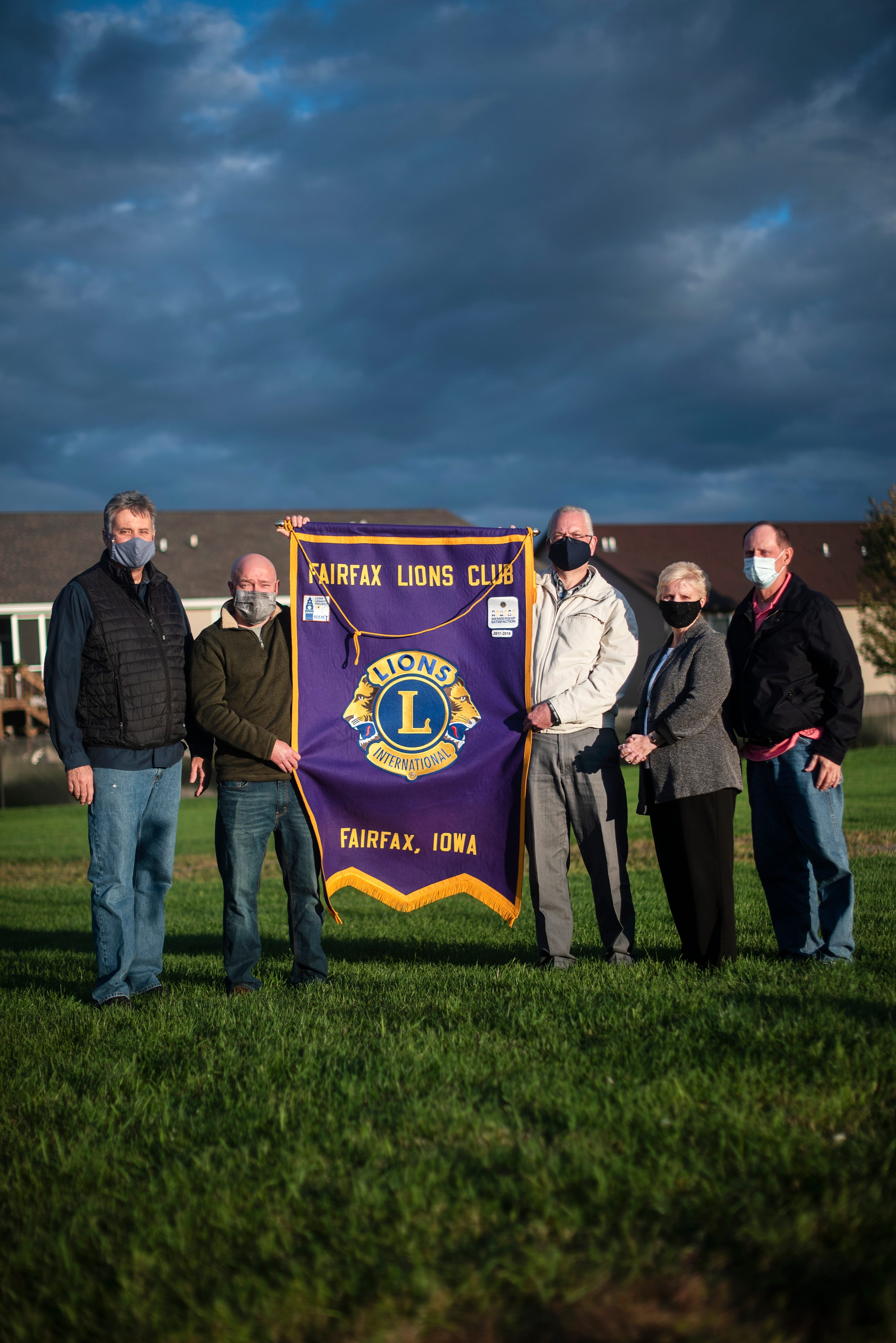 Fairfax Lions Club members Ed Faber, Dusty Weeks, Dean Schrader, Deb Mallie, and Paul Mallie pose for a portrait to honor their friend Kathy Everett, who died of COVID-19.