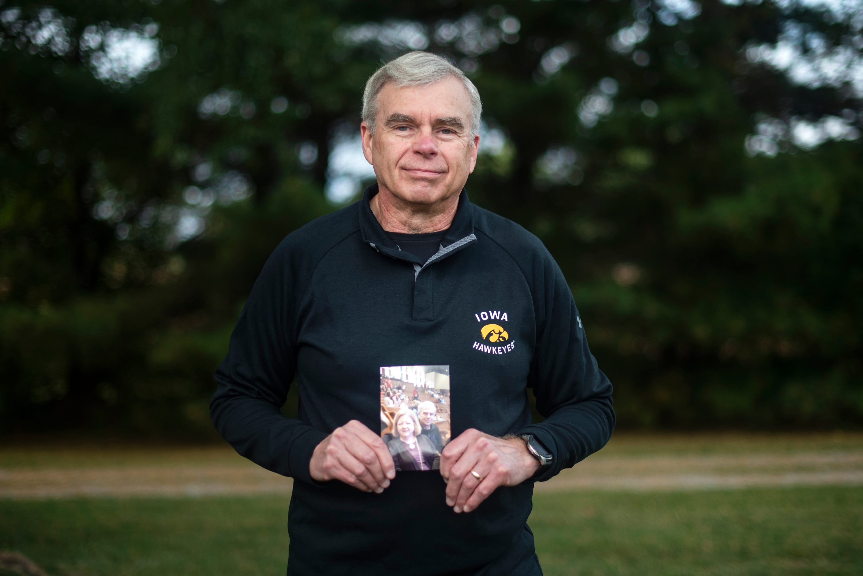 Ken Thiry holds a photo of his late wife, Regina, who died of COVID-19.