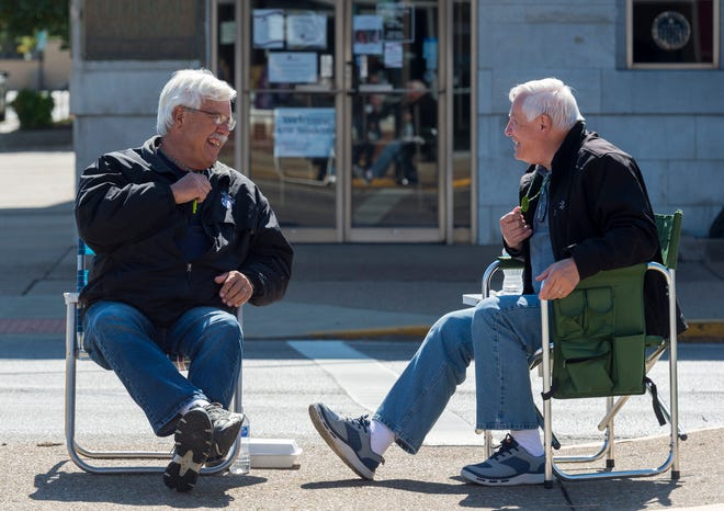 Longtime West Side Nut Club Fall Festival goers Ronald Moore, left, and David Hazelip sit on Franklin Street in their usual spot even though the 2020 festival has been canceled due to COVID-19 Monday afternoon, Oct. 5, 2020. The two decided not to break tradition so they brought their lawn chairs out on what would have been the first day of the festival.