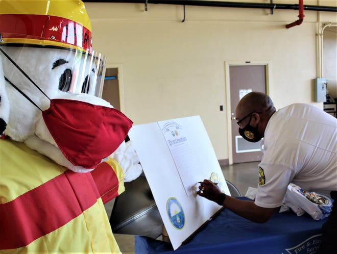 Naval Base Guam Fire Chief Gifton Lawrence signs off on fire prevention proclamation Oct. 2 as a firefighter mascot looks on.