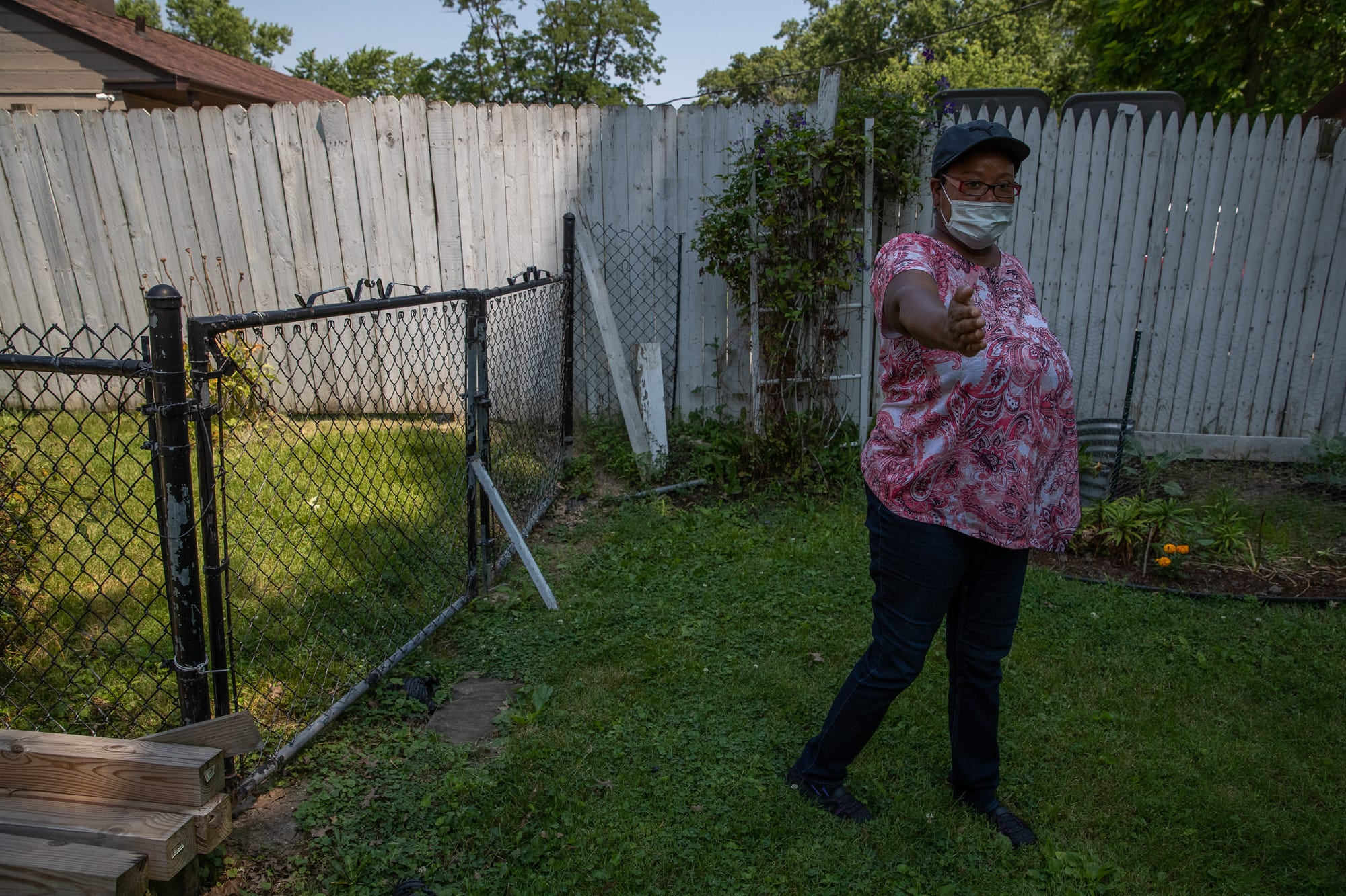 """Ella White, daughter of Gordon Mitchum, points out the path an IMPD K-9 officer walked outside Mitchum's home when searching for a suspect in a carjacking that ended on Mitchum's street, on Monday, July 6, 2020. """"This is the way he always keeps the fence, so they had to have jumped over the fence,"""" she said. White then described using bleach and water to clean up the mass amount of blood left on her father's patio."""