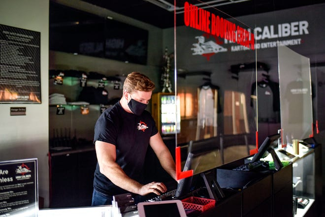 President Jordan Munsters works at a computer behind a partition recently installed to reduce the possible spread of infection on Monday, Oct. 5, 2020, at High Caliber Karting and Entertainment in the Meridian Mall in Meridian Township.