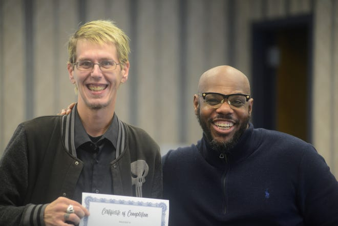 "Nathan Reed, left, was honored Monday for completing ""The Father Within Parenting Workshop,"" offered by Richland County Children Services and led by Carlos Christian, right."