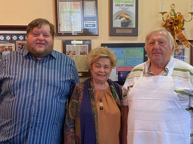 Peter, Aleksandra and George Burzynski pose in front of their wall of accomplishments at Polonez Restaurant in St. Francis.