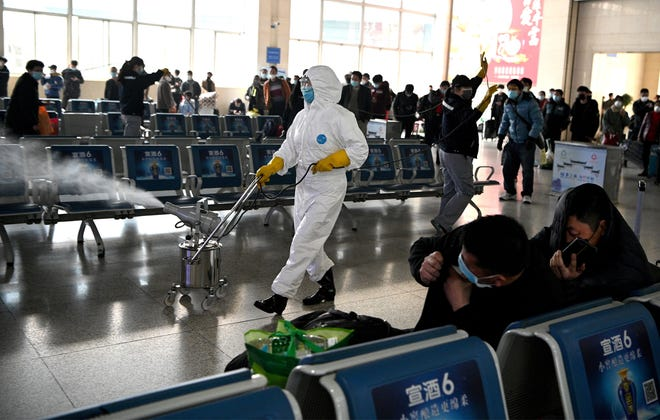 A worker in a protective suit disinfects the departure area of a railway station in China's Anhui Province in March.