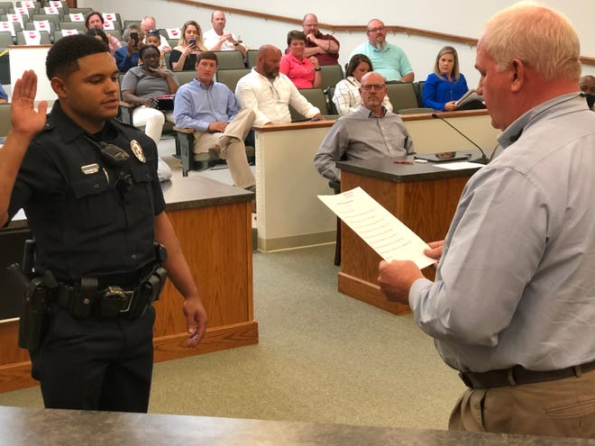 Dickson Mayor Don Weiss Jr. (right) administers the peace officer's oath to Dickson Police Department Officer Devontae Sanders (left).