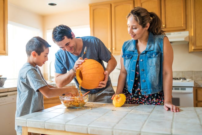 Family carving pumpkin together.