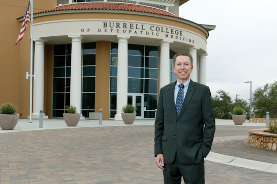 William Pieratt, the Dean and Chief Academic Officer of the Burrell College of Osteopathic Medicine, stands outside the college entrance, located on the campus of New Mexico State University in Las Cruces, N.M.