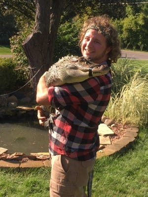 James Kozub with Puff, his alligator that escaped from his Milford yard last year, and which now has a new home at Wilderness Trails Zoo in Frankenmuth.