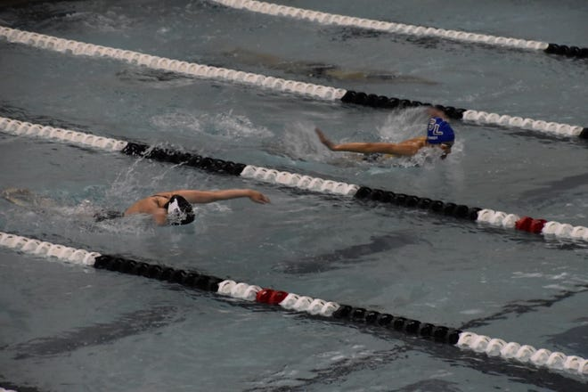 Senior Meghan Bandy swims the 100 Butterfly against South Lyon East.