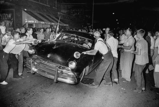 A crowd attacking cars driven by African Americans to protest integration in the schools. From 'Driving While Black.'