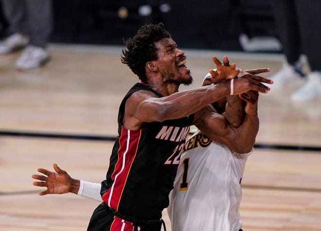 Miami Heat's Jimmy Butler (22) is fouled by Los Angeles Lakers' Kentavious Caldwell-Pope (1) during the second half in Game 3 of basketball's NBA Finals, Sunday, Oct. 4, 2020, in Lake Buena Vista, Fla. (AP Photo/Mark J. Terrill).