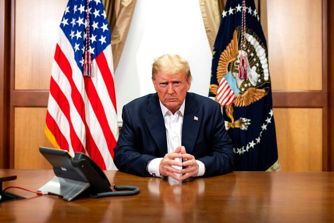 In this image provided by the White House, President Donald Trump listens during a phone call with Vice President Mike Pence, Secretary of State Mike Pompeo, and Chairman of the Joint Chiefs of Staff Gen. Mark Milley, Sunday, Oct. 4, 2020, in his conference room at Walter Reed National Military Medical Center in Bethesda, Md. White House chief of staff Mark Meadows was also in the room, but not pictured, according to the White House. (Tia Dufour/The White House via AP)