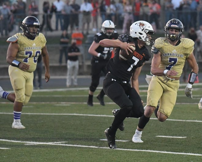 San Saba High School's Stone Sears (gold) closes in on Llano's Case Kuykendall (black) during a nondistrict football game Friday, Sept. 18, 2020, in Llano.