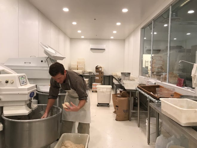 Cole Heisey, lead baker for Breadico, moves dough for ancient grains bread from a mixer to bins. Breadico is set to open its new Sioux Falls location Wednesday in the Wedge retail center at 6219 S. Western Ave.