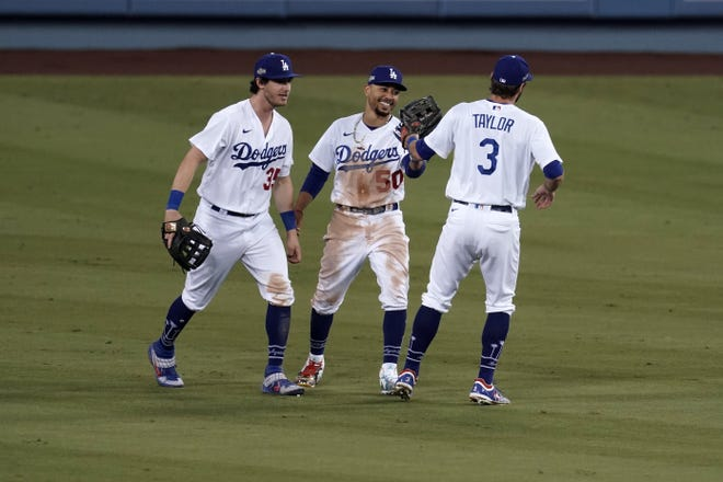 Los Angeles Dodgers center fielder Cody Bellinger (35), right fielder Mookie Betts (50) and left fielder Chris Taylor (3) celebrate at the end of Game 1 of the wild card series against the Milwaukee Brewers.