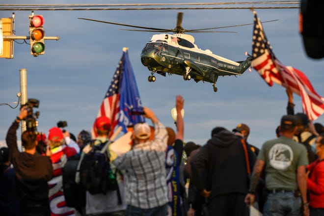 Supporters of President Donald Trump look on as he departs from Walter Reed National Military Medical Center aboard Marine One on Oct 5, 2020.
