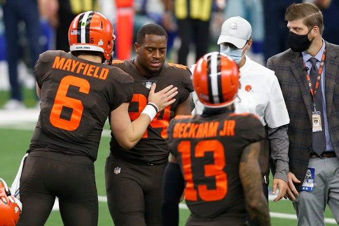 Browns running back Nick Chubb, center, leaves the field Sunday with an injury as quarterback Baker Mayfield, left, talks to him in the first quarter against the Dallas Cowboys at AT&T Stadium.