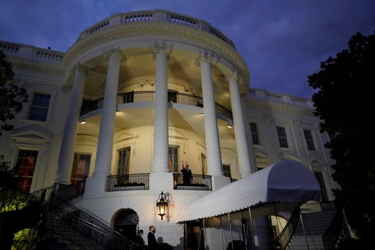 President Donald Trump salutes from the Blue Room Balcony as he returns to the White House Monday, Oct. 5, 2020, in Washington, after leaving Walter Reed National Military Medical Center, in Bethesda, Md. Trump announced he tested positive for COVID-19 on Oct. 2.