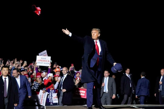 In this Sept. 30, 2020, file photo, President Donald Trump throws hats to supporters after speaking at a campaign rally at Duluth International Airport in Duluth, Minn. President Trump and first lady Melania Trump have tested positive for the coronavirus, the president tweeted early Friday.