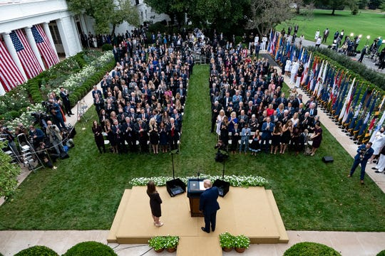 President Donald Trump, center, stands with Judge Amy Coney Barrett as they arrive for a news conference to announce Barrett as his nominee to the Supreme Court, in the Rose Garden at the White House in Washington on Sept. 26, 2020.