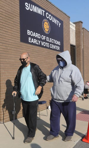 John Doll, left, is helped Tuesday by his friend Don Joiner into the Summit County Board of Elections in Akron, where Doll collapsed. Doll was taken away by an ambulance.
