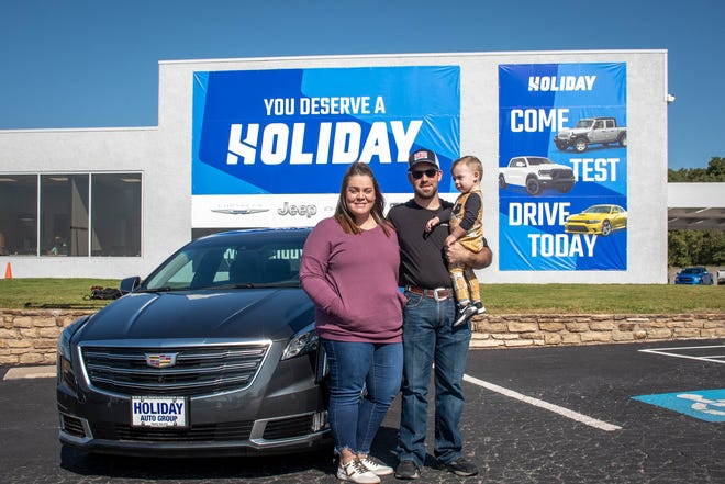 Brittany Miller (left), Kalub Miller (center) and Kayden Miller (right) stand next to the new cadillac that was presented to them by Holiday Auto Group on Monday, Oct. 5.
