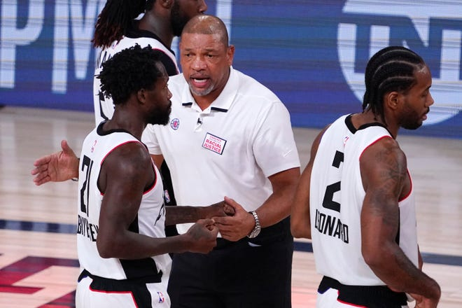 Clippers coach Doc Rivers congratulates Patrick Beverley as Kawhi Leonard walks past after a playoff win.