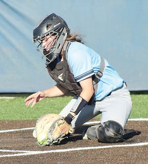 Catcher Brandi Woods scoops a pitch out of the dirt earlier this season for the Bartlesville High softball team.