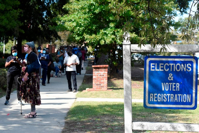 Voters wait in line outside the Richland County election office on the first day of in-person absentee voting in South Carolina on Monday in Columbia.