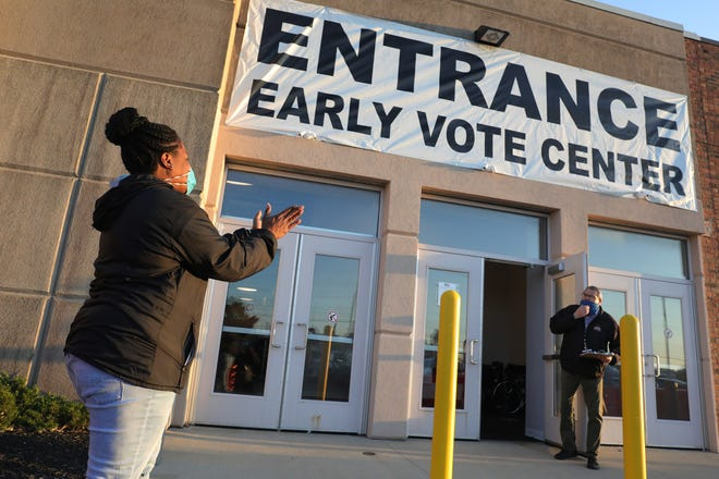 Sharine Jordan, standing outside the Franklin County Board of Elections, claps as a door is opened for early voting at 8am on Tuesday, October 6, 2020. Sharine arrived at 5am to be the first inline.