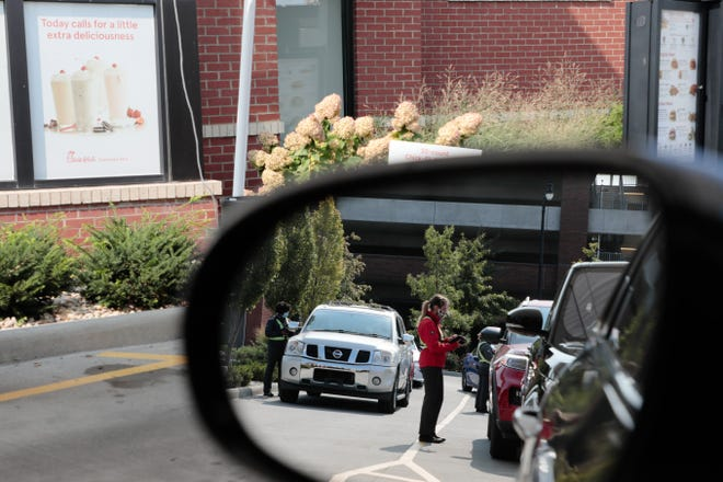 Employees take orders as drivers wait in the Chick-fil-A drive-thru on Tuesday in Grandview Heights. The ongoing COVID-19 pandemic has caused increases for wait times at fast-food restaurants, and Chick-Fil-A has one of the longest wait times in the country, but also scores high on customer satisfaction.