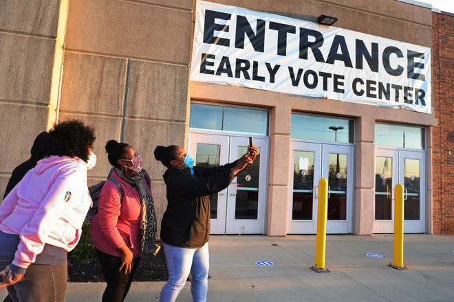 Sharine Jordan, far right, takes a selfie with Chrystal Alexander, second from right, Puella Jordan, third from right, and Kim Booker, hidden, outside the Franklin County Board of Elections in Columbus, just before the doors opened to early voters at 8 a.m. on Tuesday, Oct. 6, 2020. Sharine arrived at 5am to be the first in line.
