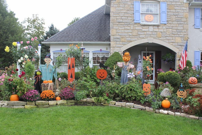 Linda Laine of Westerville incorporates her decorations into the garden in front of her Westerville home. The scarecrows, witches, ghosts and pumpkins join mums, late season perennials and dahlias that keep blooming until a freeze, Laine said.