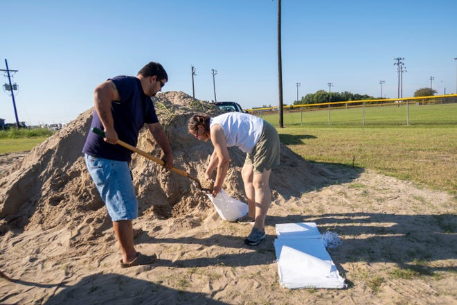 Residents fill sandbags during a recent storm.