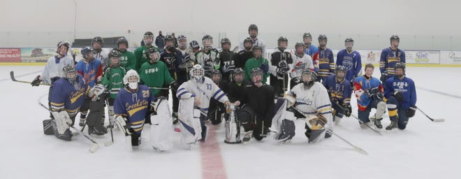 The players pose for a group picture after the Crookston Blue Line Club's Peewee 3v3 Stanley Cup tournament.