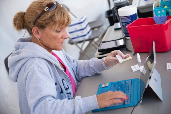 A health care worker processes a COVID-19 rapid test at the Lake Square Mall. [Cindy Peterson/Correspondent]