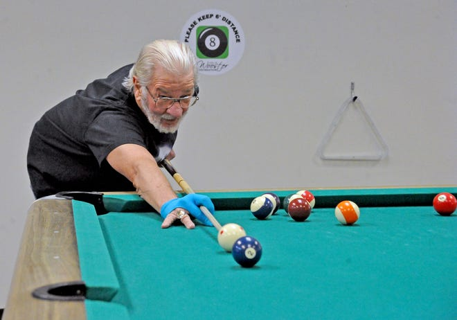 Ray Starkey practices on his billiards at the Wooster Community Center on Tuesday. The center reopened Monday after being closed for seven months due to COVID-19.