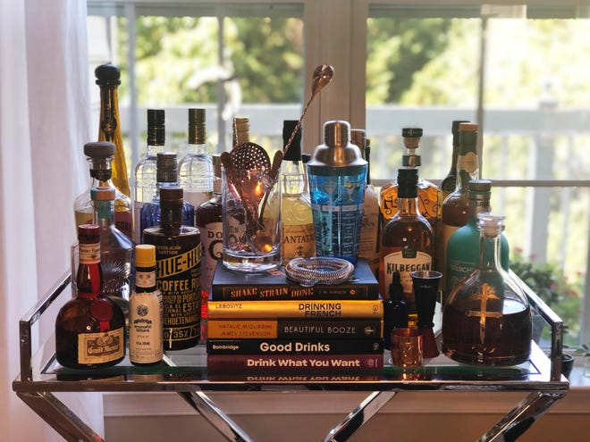 A collection of spirits and new cocktail recipe books are displayed. Since the pandemic hit the United States, a lot of social drinking has moved back home. The books can help would-be mixologists.
